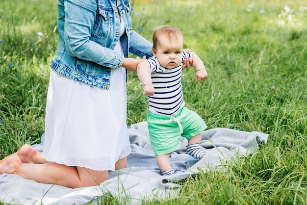 Schattige blanke babyjongen n een gestreept t-shirt. picknick in het zomerpark. eerste stappen.