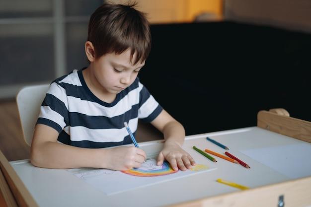 Schattige blanke jongen van elementaire leeftijd die een regenboog tekent met potloden die aan het bureau in zijn kamer thuis zitten. hoge kwaliteit foto