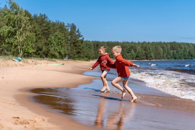 Schattige blanke jongens met rode hoodies en blauwe onderbroeken die wegrennen van de golven in het meer van ladoga