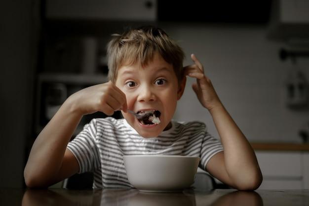 Schattige blanke kleine jongen in gestreept t-shirt die pap eet met wijd open mond Premium Foto