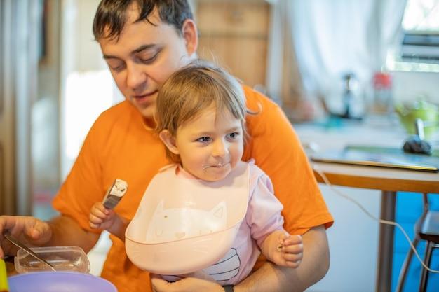 Schattige blanke peuter zit met vader aan tafel. vader die baby voedt, alleenstaande ouder met klein kind