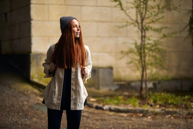 Schattige blanke roodharige vrouw in jas en hoed reiziger met rugzak wandelen in historische en een...