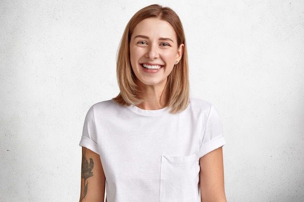 Schattige blanke vrouw met een positieve uitdrukking, heeft witte perfecte tanden, een gezonde huid, een tatoeage op de arm, kort haar verheugt zich over goed nieuws