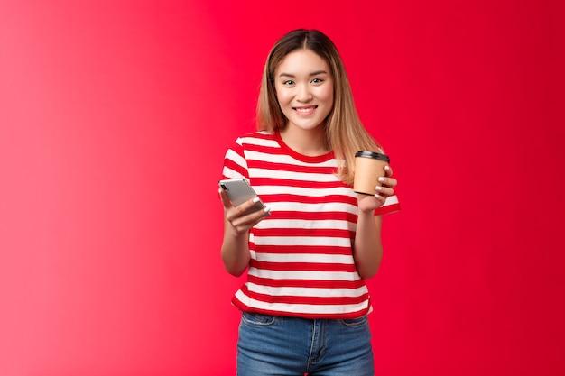 Schattige blonde aziatische universiteitsstudente staat lunchpauze geniet van koffie in de buurt van campus hold smartphone ...