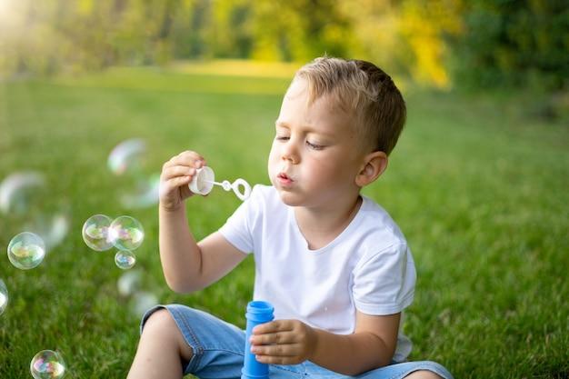 Schattige blonde baby blaast zeepbellen op in de zomer op een groen gazon, plezier, openluchtrecreatie