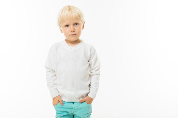 Schattige blonde baby in een wit t-shirt op een witte muur met kopie ruimte