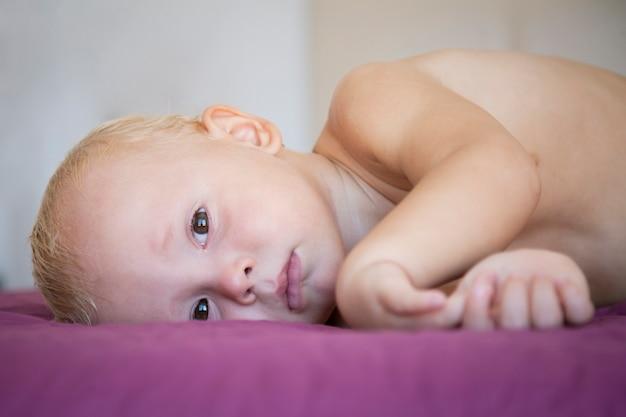 Schattige blonde baby liggend op het bed en huilt. huilende jongen kruipen in bed in de kamer. jeugd. droefheid.