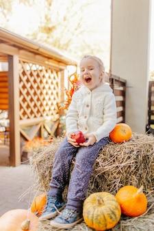Schattige blonde baby peuter in witte gebreide jas zittend op de hooiberg met pompoenen op veranda, spelen met appel en lachen