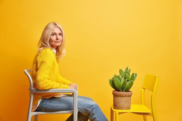 Schattige blonde dame van middelbare leeftijd in vrijetijdskleding zit op stoel tegenover pot met cactus