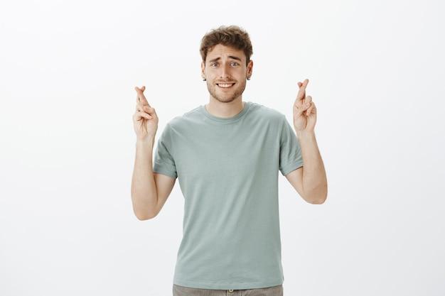 Schattige blonde europese mannelijke student in t-shirt gekruiste vingers opheffen en lachend met verlegen en onhandige uitdrukking