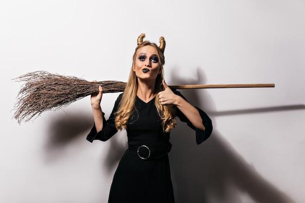 Schattige blonde heks die van halloween-fotoshoot geniet. elegant vampiermeisje in de lange bezem van de kledingsholding.