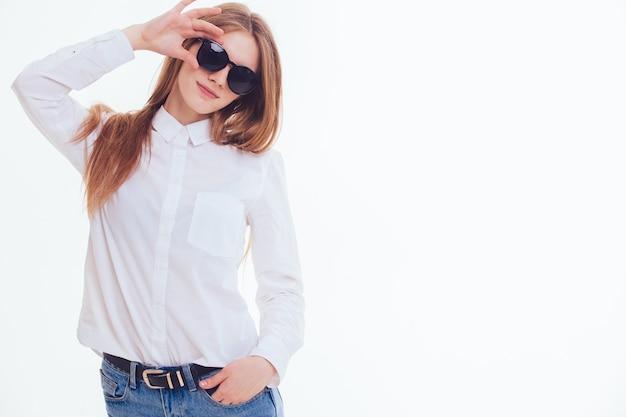 Schattige blonde houdt de zonnebril in de studio op een witte achtergrond. isolatie.