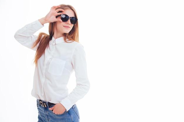 Schattige blonde houdt de zonnebril in de studio op een witte achtergrond. isolatie. Premium Foto