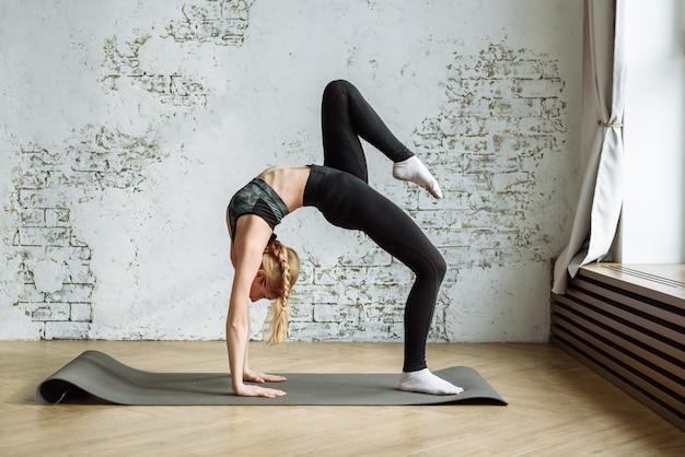 Schattige blonde houdt zich bezig met fitness op de muur van een witte bakstenen muur thuis tijdens quarantaine