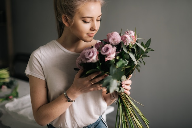 Schattige blonde jonge vrouw die modekleren draagt, snuift een boeket bloemen