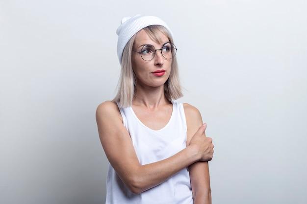 Schattige blonde jonge vrouw met een bril, een witte hoed kijkt naar de zijkant op een lichte achtergrond.