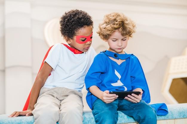 Schattige blonde jongen en zijn afrikaanse vriend in kostuums van superman kijken naar nieuwsgierige dingen in smartphone na het spelen