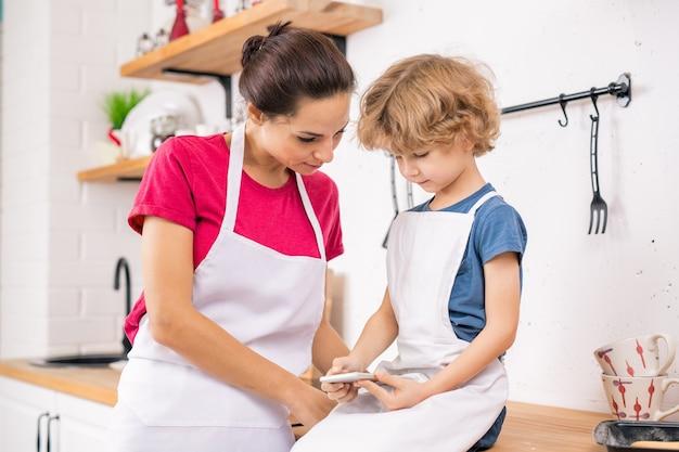 Schattige blonde jongen in schort met smartphone terwijl hij zijn moeder nieuw recept van lekker eten in de keuken laat zien