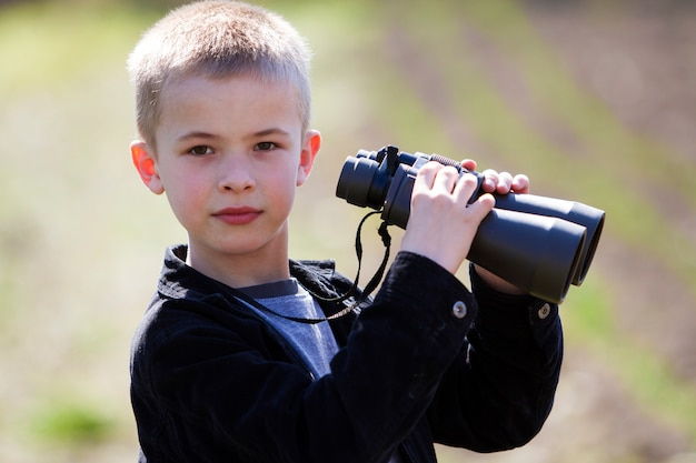 Schattige blonde jongen kijkt door een verrekijker op afstand op onscherpe achtergrond