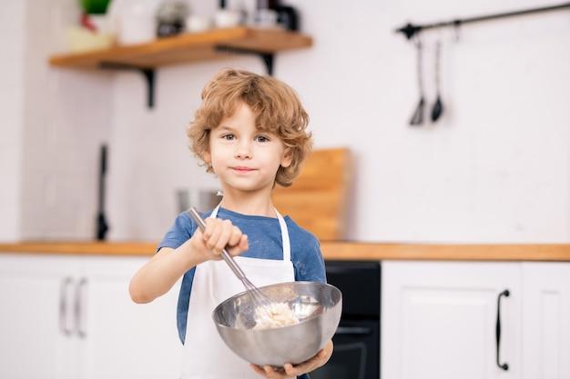 Schattige blonde jongen met behulp van bakkebaard tijdens het mengen van bloem en eieren in stalen kom in keukenomgeving