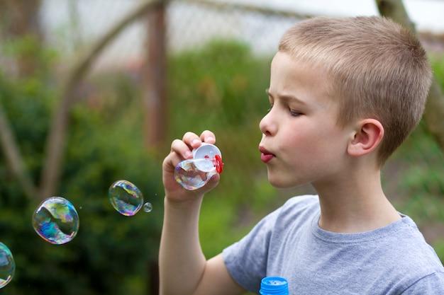 Schattige blonde jongen met ernstige uitdrukking blazen kleurrijke transparante zeepbellen