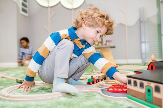 Schattige blonde jongetje in vrijetijdskleding spelen op de vloer met speelgoedtreinen en huis in de kleuterschool of kindercentrum