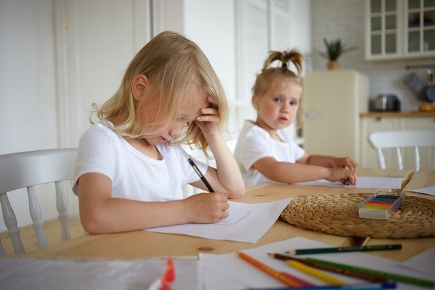Schattige blonde kleine jongen huiswerk, pen vasthouden, iets tekenen op een vel papier met zijn mooie zusje zittend op de achtergrond. twee kinderen maken van tekeningen aan houten tafel in de keuken