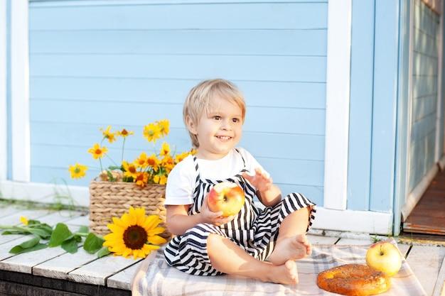 Schattige blonde kleine jongen met een appel en een broodje in zijn handen op de veranda van een houten huis op zomerdag