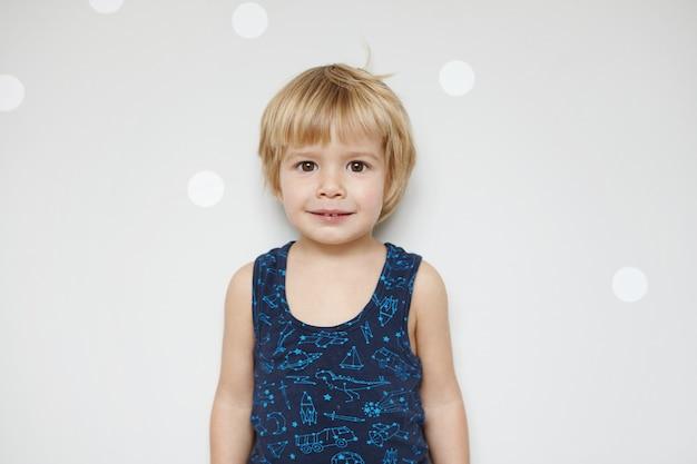 Schattige blonde mannelijke peuter met blond haar en mooie bruine ogen met glimlach, staande tegen een witte muur met kopie ruimte voor uw promotionele inhoud