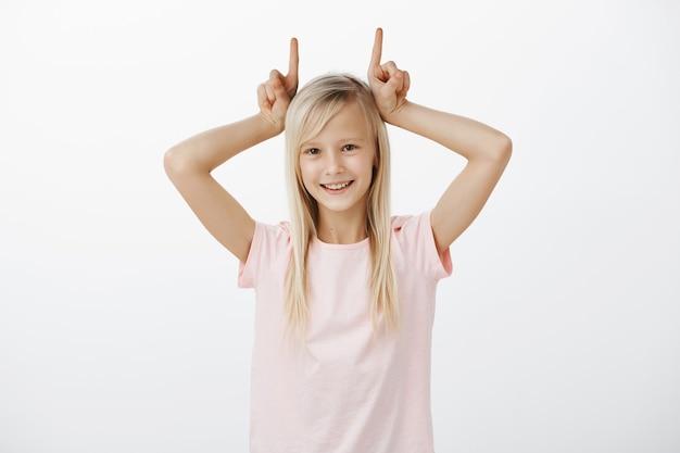 Schattige blonde meisje duivel hoorns tonen en glimlachen