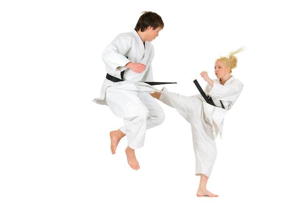 Schattige blonde meisje en een jonge brutale kerel karate zijn betrokken bij de opleiding in een kimono op een wit