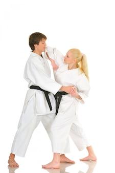 Schattige blonde meisje en een jonge brutale kerel karate