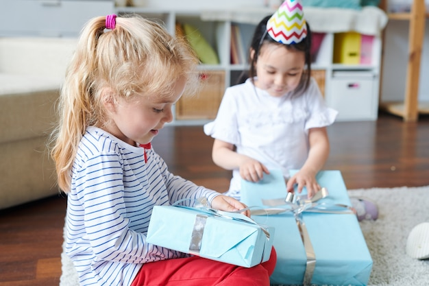Schattige blonde meisje haar verjaardagscadeau met haar vriend uitpakken terwijl beiden thuis op de vloer zitten