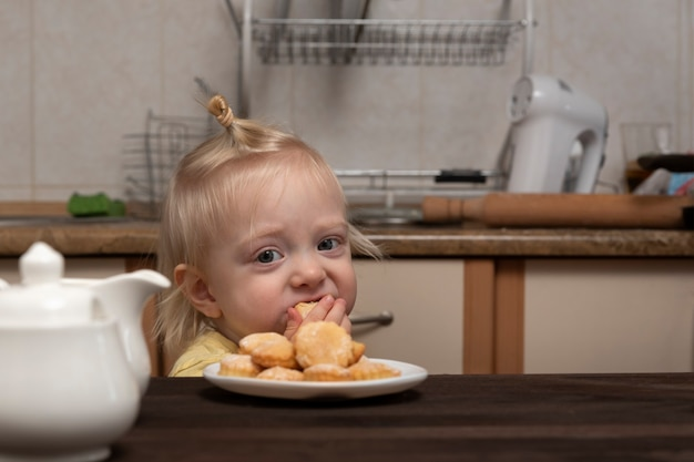 Schattige blonde meisje is ontbijten in de keuken en kijken naar de koekjes