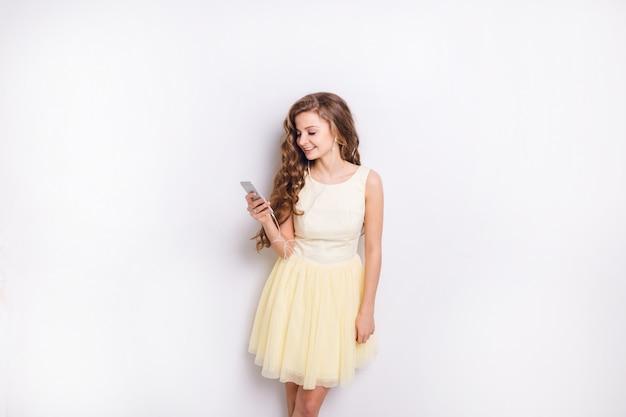 Schattige blonde meisje, luisteren naar muziek op oortelefoons op smartphone is plezier. ze glimlacht breed en speelt met haar gele jurk. ze had lang blond krullend haar