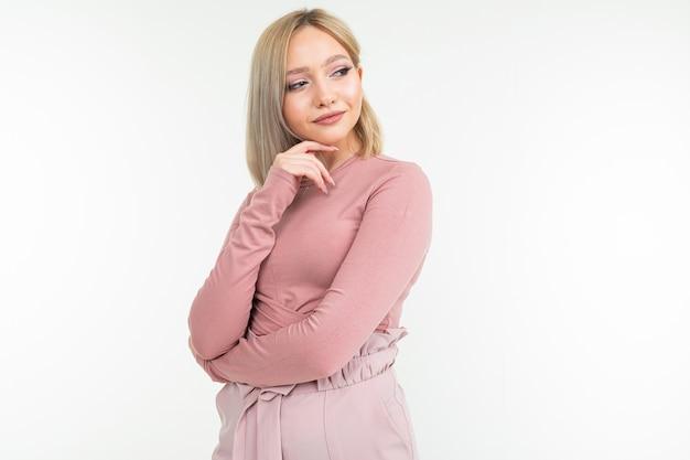 Schattige blonde meisje met een kort kapsel denkt mysterieus op een witte studio achtergrond met kopie ruimte.