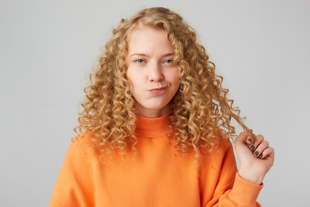 Schattige blonde met krullend haar en blauwe ogen die achterdochtig naar de voorkant kijken, houdt een haarlok vast en denkt aan iets