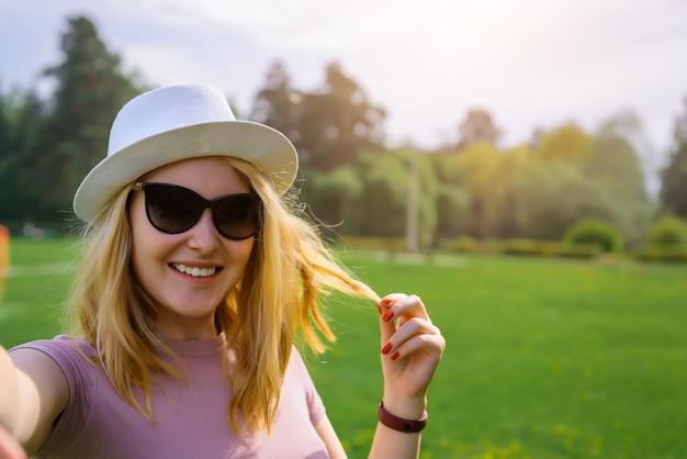 Schattige blonde neemt selfie in groene zomer park, vakantie concept.