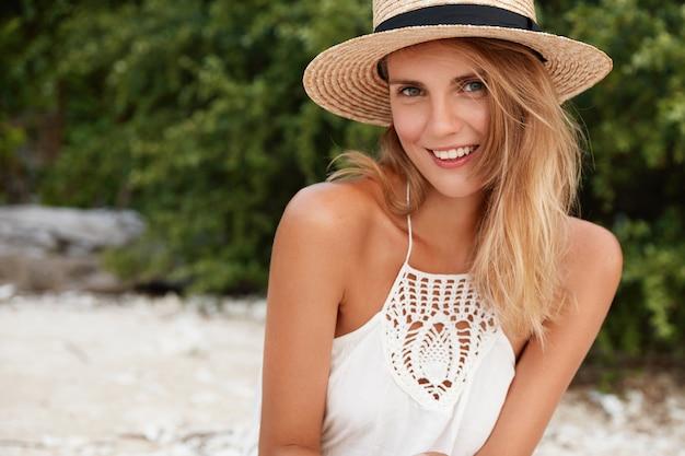 Schattige blonde tevreden vrouw gekleed in zomerkleding, vormt buiten op het strand tegen de groene vegetatie, geniet van zonnig weer, brengt vakantie door aan zee. mensen, vrije tijd, schoonheidsconcept