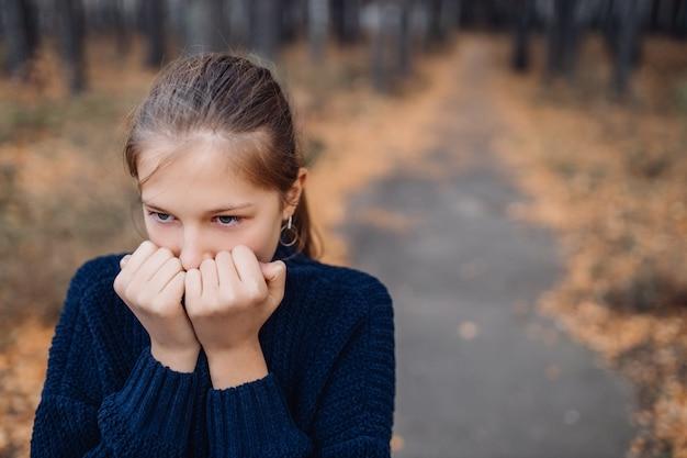Schattige blonde tiener in herfst park. jong meisje dat zich op bos bevindt