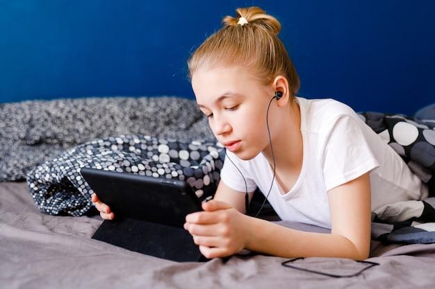 Schattige blonde tiener meisje kijken naar video op smartphone