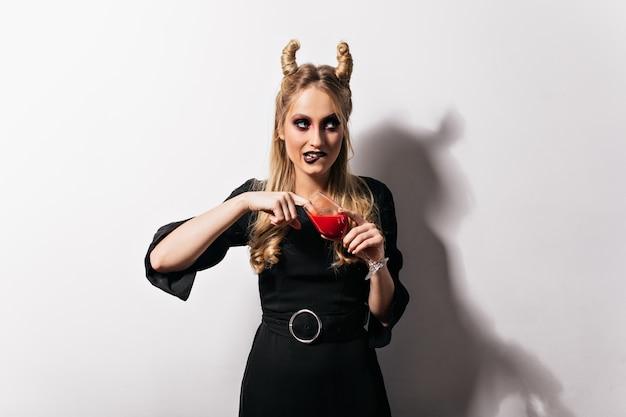 Schattige blonde vampier in jurk staande op een witte muur. vrij slank meisje dat bloed drinkt in halloween.