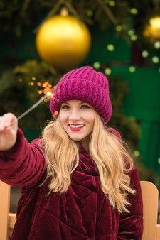Schattige blonde vrouw die plezier heeft met sprankelende bengaalse lichten op de nieuwjaarsspar in kiev