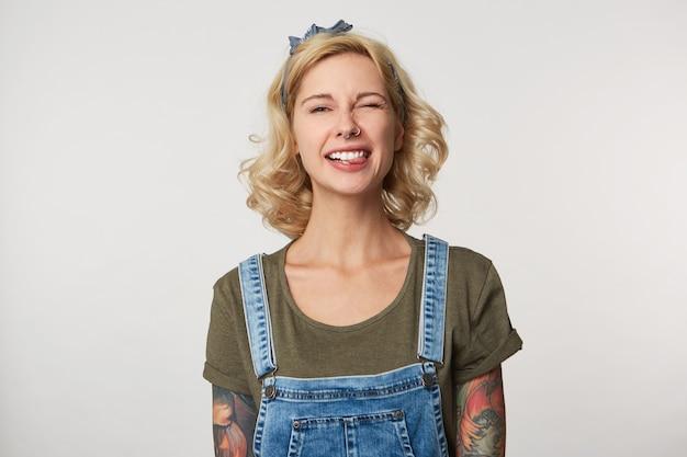 Schattige blonde vrouw draagt denim overalls, casual t-shirt, glimlacht en toont haar tong op grijs
