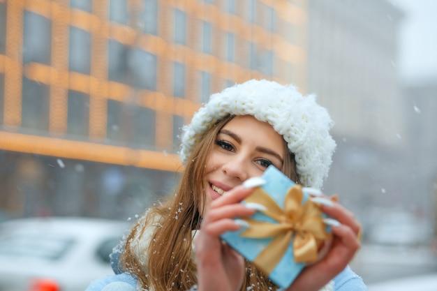 Schattige blonde vrouw draagt een witte gebreide muts met een blauwe geschenkdoos, wandelend in de stad tijdens de sneeuwval