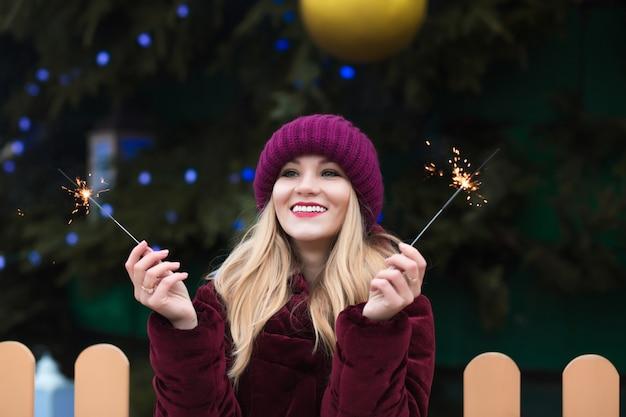 Schattige blonde vrouw gekleed in gebreide muts en warme jas met gloeiende sterretjes bij de kerstboom