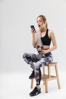Schattige blonde vrouw gekleed in sportkleding met smartphone zittend op een stoel na een training in de sportschool geïsoleerd over een witte muur
