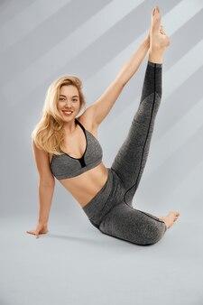 Schattige blonde vrouw in trendy sportkleding doet stretching