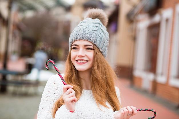 Schattige blonde vrouw in warme gebreide muts poseren met kerstsnoepjes op straat