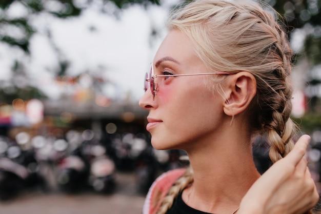 Schattige blonde vrouw in zonnebril haar vlechten aan te raken.